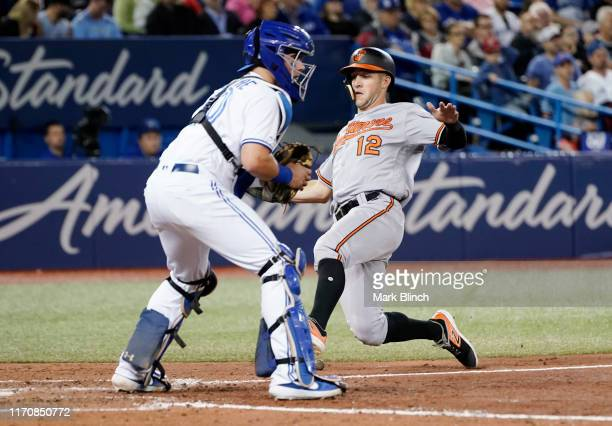 Stevie Wilkerson of the Baltimore Orioles comes home to score against Reese McGuire of the Toronto Blue Jays in the sixth inning during their MLB...