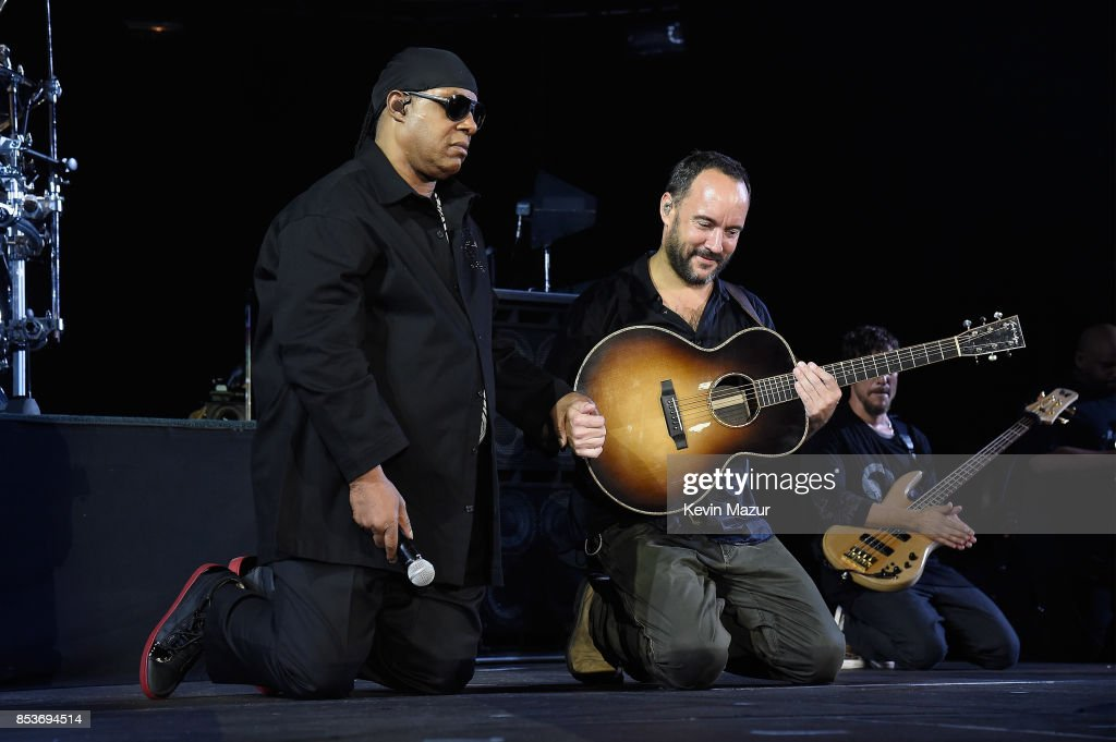 Stevie Wonder (L) and Dave Matthews kneel onstage at 'A Concert for Charlottesville,' at University of Virginia's Scott Stadium on September 24, 2017 in Charlottesville, Virginia. Concert live-stream presented in partnership with Oath.