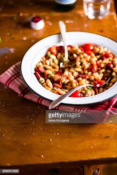 stew with sausages, white kidney beans and cherry tomatoes, selective focus - cultura húngara - fotografias e filmes do acervo