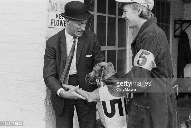 Steward and owner being friendly with affectionate greyhound at Clapton Greyhound Stadium, London, UK, circa 1968.