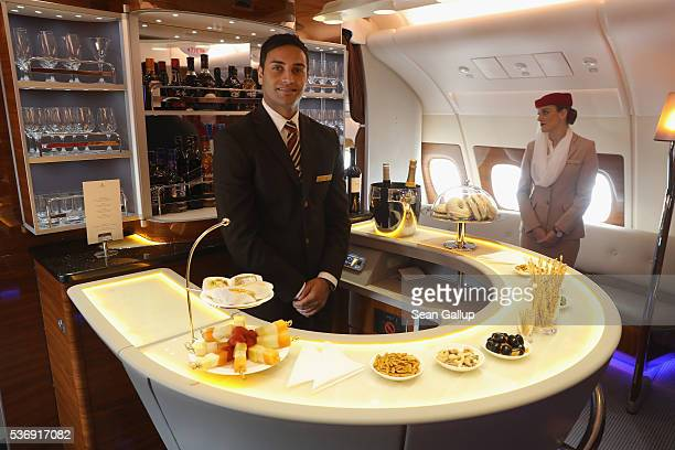 A steward and stewardess welcome visitors at the bar in business class on board an Emirates A380 passenger plane at the ILA 2016 Berlin Air Show on...