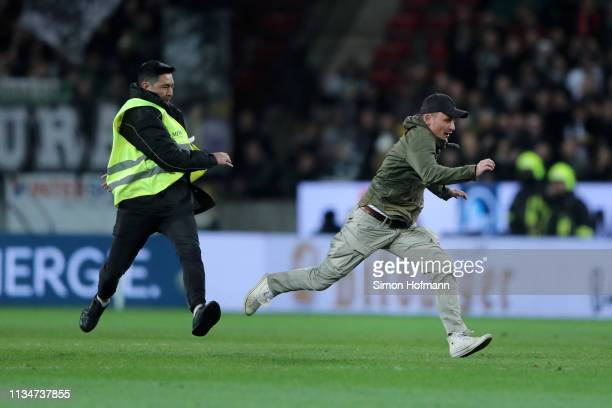 Steward chases a pitch invader during the Bundesliga match between 1. FSV Mainz 05 and Borussia Moenchengladbach at Opel Arena on March 09, 2019 in...