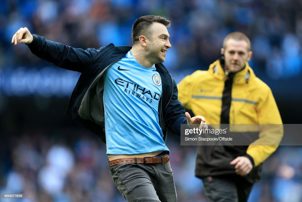 A steward chases a pitch-invader at the end of the Premier League match between Manchester City and Swansea City at the Etihad Stadium on April 22, 2018 in Manchester, England.