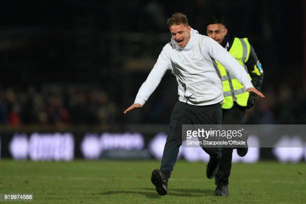 A steward chases a pitchinvader during The Emirates FA Cup Fifth Round match between Rochdale AFC and Tottenham Hotspur at Spotland Stadium on...