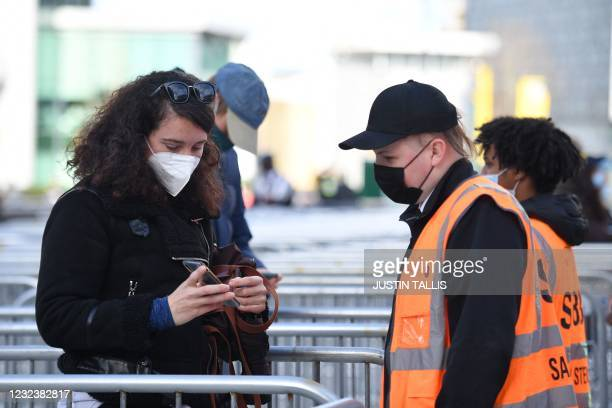 Steward checks the Covid-19 test results of a spectator arriving at Wembley Stadium ahead of the English FA Cup semi-final football match between...