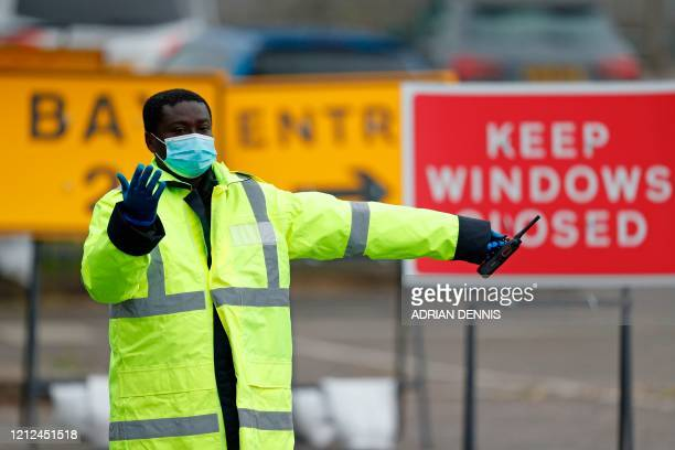 A steward directs a car at the coronavirus COVID19 testing centre set up in the car park of Chessington World of Adventures south of London on May 10...