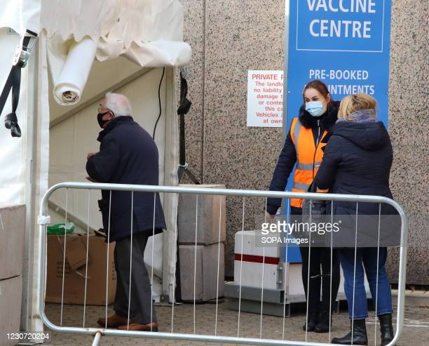 Steward directs and elderly man into the vaccination centre. A steady stream of elderly people with pre-booked appointments at the new Covid-19...