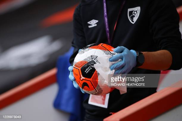 Steward disinfect a ball before the English Premier League football match between Bournemouth and Tottenham Hotspur at the Vitality Stadium in...