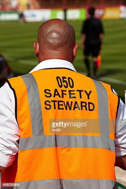 Steward in orange jacket at football stadium entrance