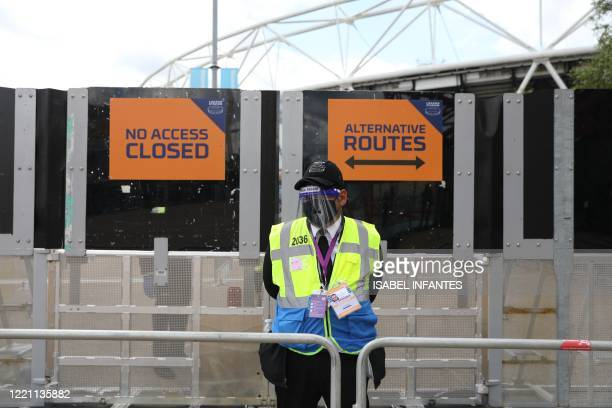 Steward in PPE including face mask and visor as a precaution against COVID-19 staffs a barrier at The London Stadium, in east London on June 20, 2020...
