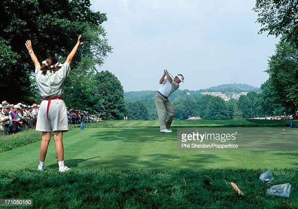 A steward indicates silence as Johnny Miller of the United States tees off during the US Open Golf Championship held at the Oakmont Country Club in...
