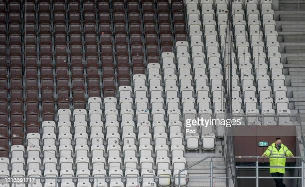 A steward is seen in the empty stands during the Second Bundesliga match between FC St Pauli and 1 FC Nürnberg at Millerntor Stadium on May 17 2020...