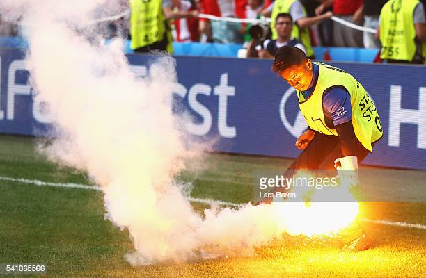 A steward picks up a flare which was thrown onto the pitch by supporters during the UEFA EURO 2016 Group F match between Iceland and Hungary at Stade...