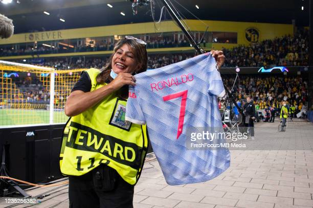 Steward poses with the jersey received by Cristiano Ronaldo after the UEFA Champions League group F match between BSC Young Boys and Manchester...