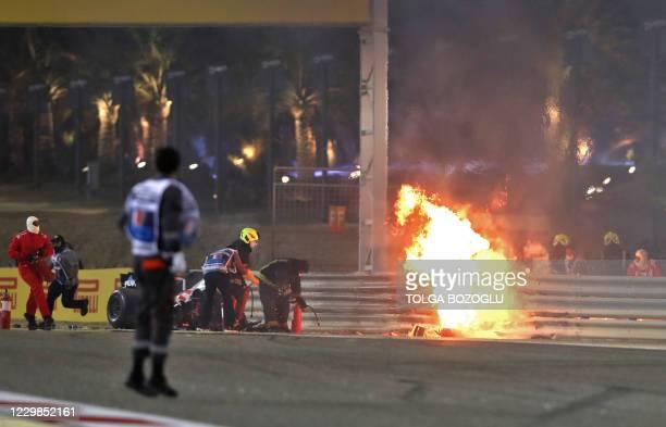 Steward reacts as officials put out a fire on Haas F1's French driver Romain Grosjean car following a crash during the Bahrain Formula One Grand Prix...