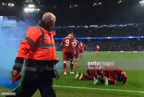 A steward removes a flare as Liverpool's Egyptian midfielder Mohamed Salah celebrates scoring his team's first goal qith Liverpool's Senegalese...