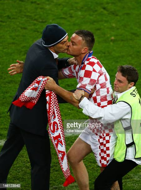 Steward restrains a pitch invader as he kisses to Head Coach Slaven Bilic of Croatia during the UEFA EURO 2012 group C between Ireland and Croatia at...