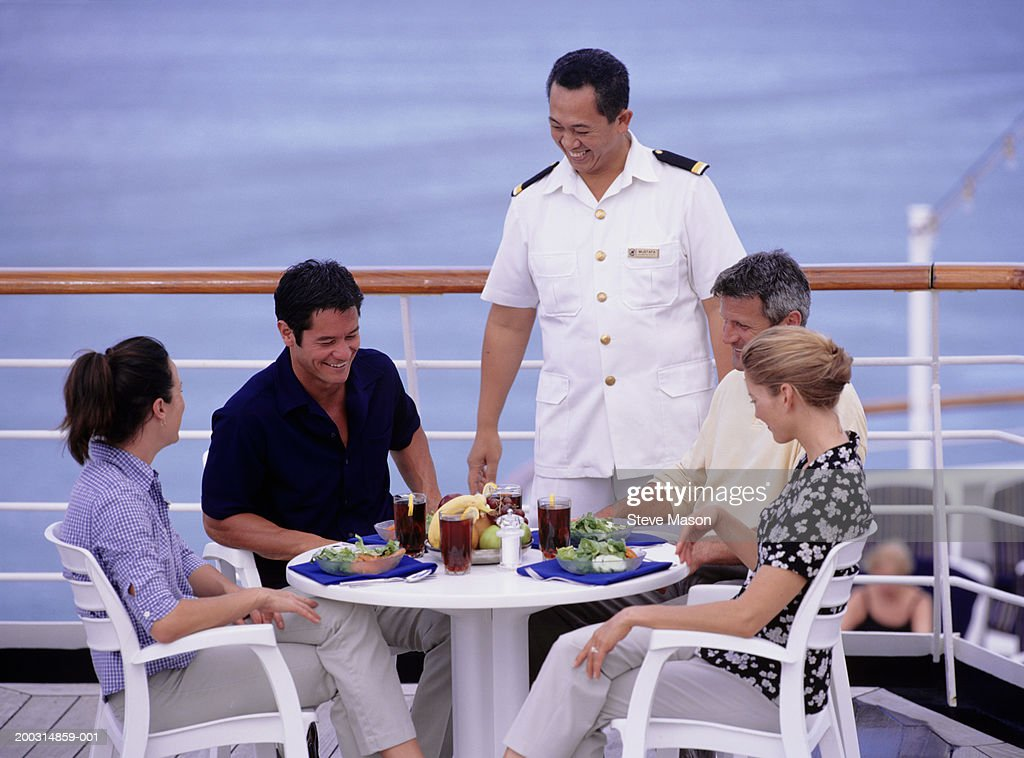 Steward Serving Lunch To Two Couples On Deck Of Cruise Ship Stock - Steward cruise ship