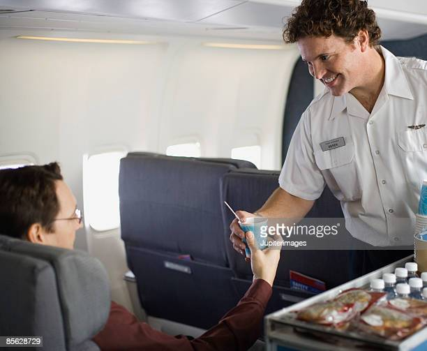 Steward serving passenger on airplane