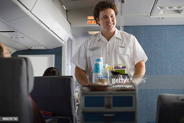Steward serving passengers on airplane