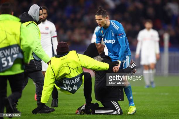 Steward slips as he tries to apprehend a pitch invader kneeling in front of Cristiano Ronaldo of Juventus during the UEFA Champions League round of...