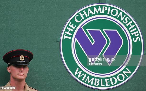 A steward standing by the All England Club crest during the First Round match between Rafael Nadal and Andreas Beck on Day 2 of the Wimbledon...