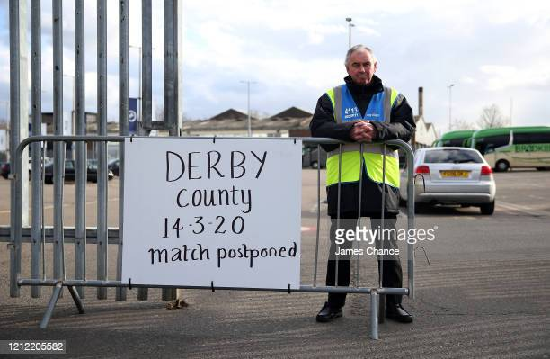 Steward stands behind a home made sign displaying a message of the Sky Bet Championship match between Millwall FC and Derby County will be postponed...