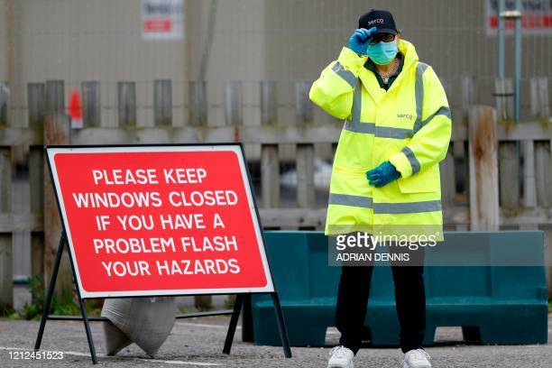 Steward stands ready to help people arriving at the coronavirus COVID-19 testing centre set up in the car park of Chessington World of Adventures,...