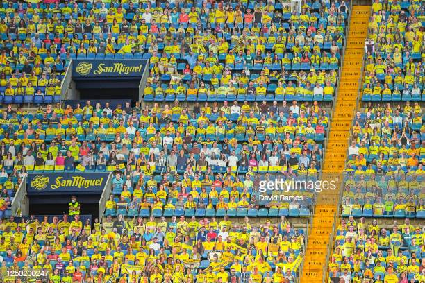 Steward stands while wearing a face mask amongst Cardboard cut outs of Villarreal supporters are seen in the stands during the Liga match between...