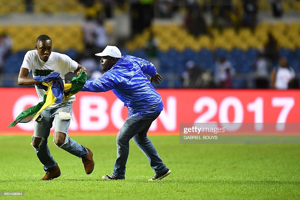 A steward stops a Gabon supporter who invaded the pitch at the end of the 2017 Africa Cup of Nations group A football match between Cameroon and Gabon at the Stade de l'Amitie Sino-Gabonaise in Libreville on January 22, 2017. / AFP / GABRIEL