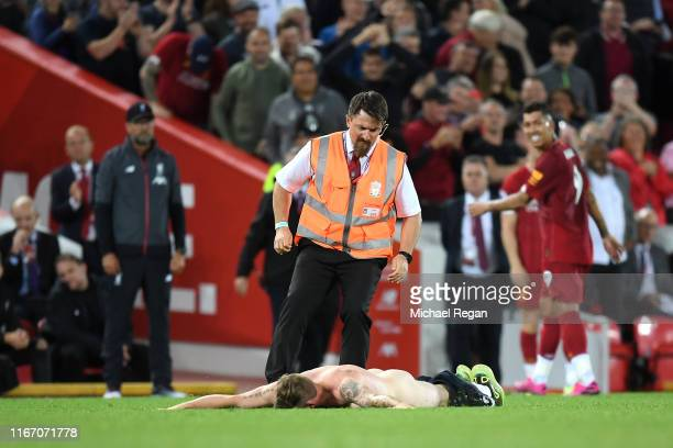 A steward stops a pitch invader during the Premier League match between Liverpool FC and Norwich City at Anfield on August 09 2019 in Liverpool...