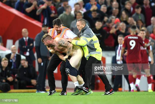 Steward stops a pitch invader during the Premier League match between Liverpool FC and Norwich City at Anfield on August 09, 2019 in Liverpool,...