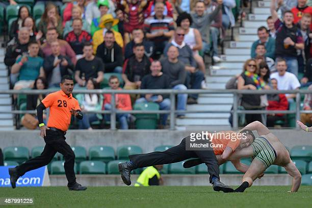 A steward tackles a fan who ran on the pitch during the Babcock Trophy rugby union match between The British Army and the Royal Navy played in...