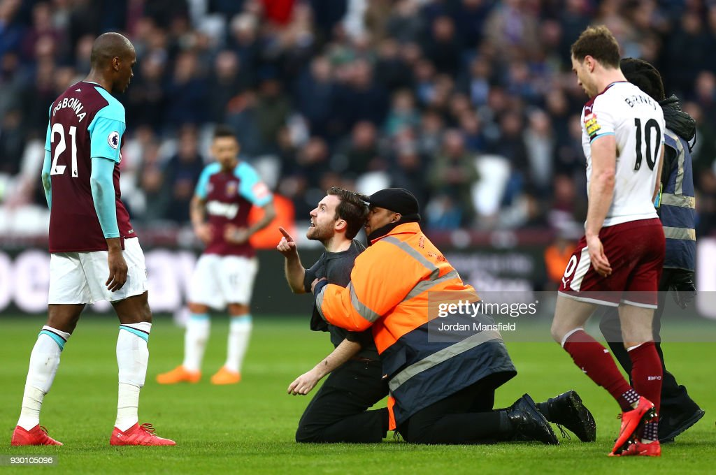 A steward tackles a pitch Invader during the Premier League match between West Ham United and Burnley at London Stadium on March 10, 2018 in London, England.