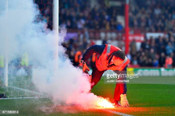 A steward takes a flare from the pitch during the Sky Bet Championship match between Brentford and QPR at Griffin Park on April 22 2017 in Brentford...