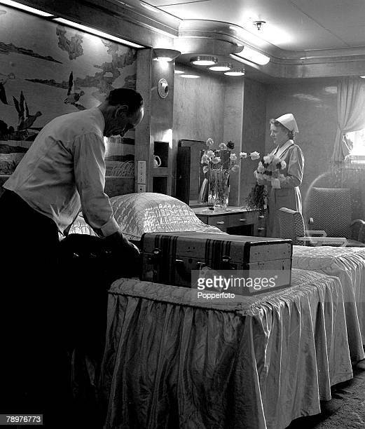 1948 A steward unpacks a passengers clothes in one of the state rooms while a stewardess fixes a vase of flowers which have been sent aboard the...
