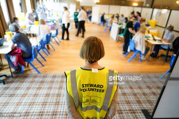 Steward volunteer watches over patients as they receive their Pfizer-BioNTech COVID-19 vaccines at the Hexham Mart Vaccination Centre on May 13, 2021...