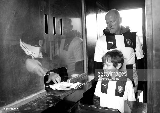 Steward wearing a storm trooper mask scans match tickets as fans enter through the turnstiles prior to the Vanarama National League match between...