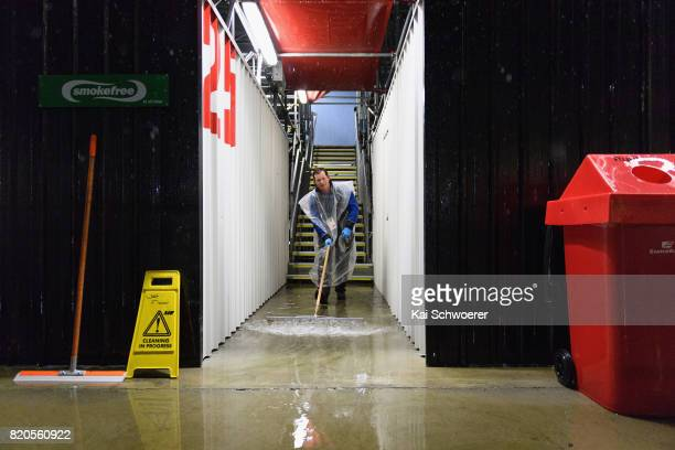 A steward works to dry the stands due to heavy rainfall prior to the Super Rugby Quarter Final match between the Crusaders and the Highlanders at AMI...