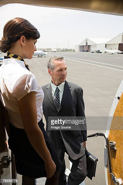 Stewardess and businessman boarding jet