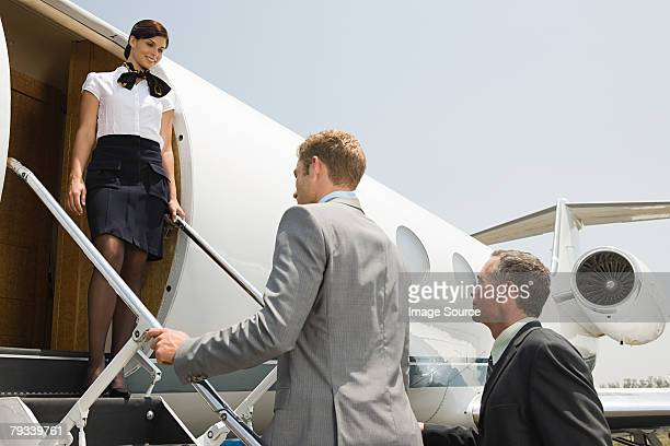 Stewardess and businessmen boarding jet