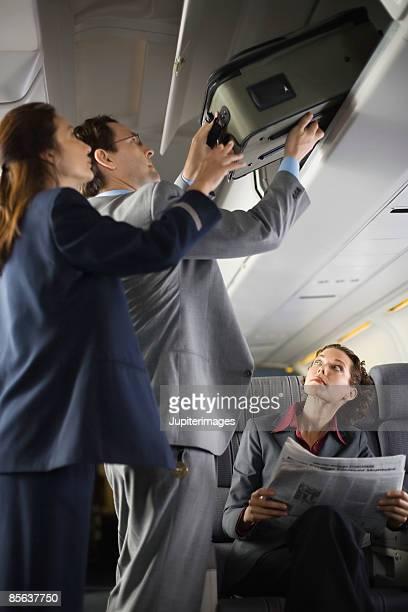 Stewardess assisting passenger with luggage
