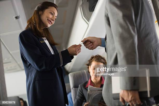 Stewardess assisting passenger with seating assignment
