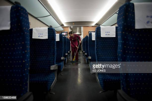 A stewardess cleans the floor of a highspeed train during a journey for journalists through Hebei province south of Beijing on December 22 2012 China...
