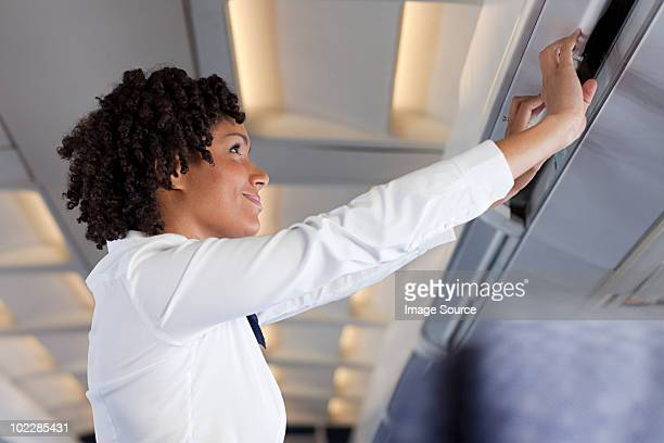stewardess closing locker on airplane - flight attendant stock pictures, royalty-free photos & images