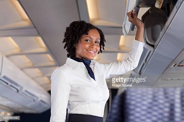 Stewardess closing locker on airplane