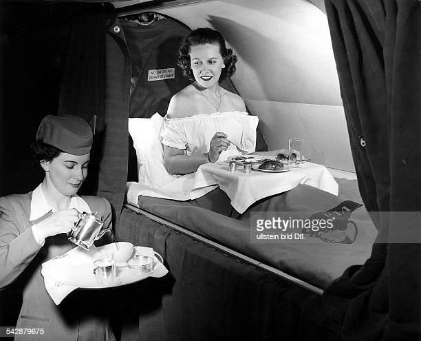 Stewardess der Fluggesellschaft PanAmerican World Airways System serviert einerFlugpassagierin das Frühstück im Bettwährend eines Transatlantikfluges...