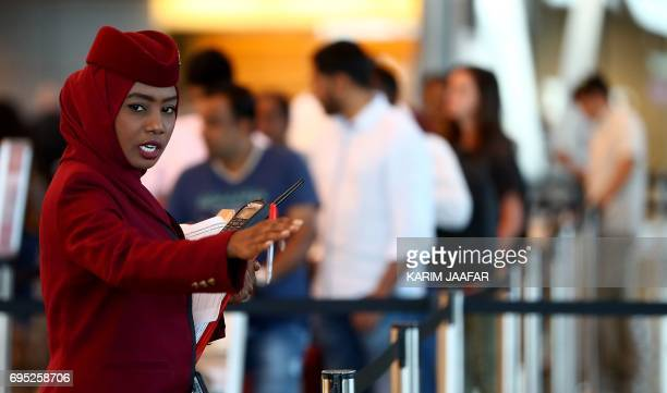 A stewardess directs passengers at the checkin area in the Hamad International Airport in the Qatari capital Doha on June 12 2017 Qatar Airways...