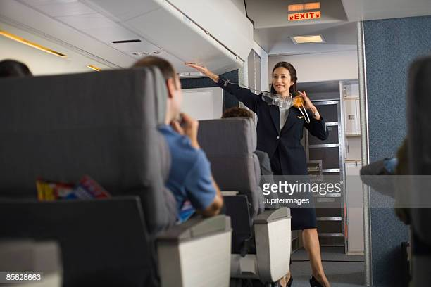 Stewardess explaining safety procedures to passengers on airplane