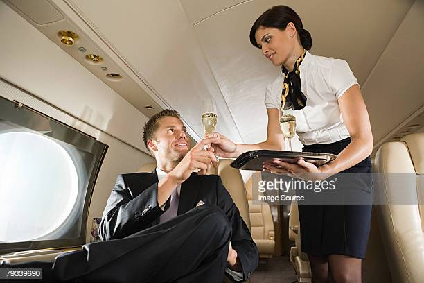 stewardess handing champagne to man - crew stock pictures, royalty-free photos & images